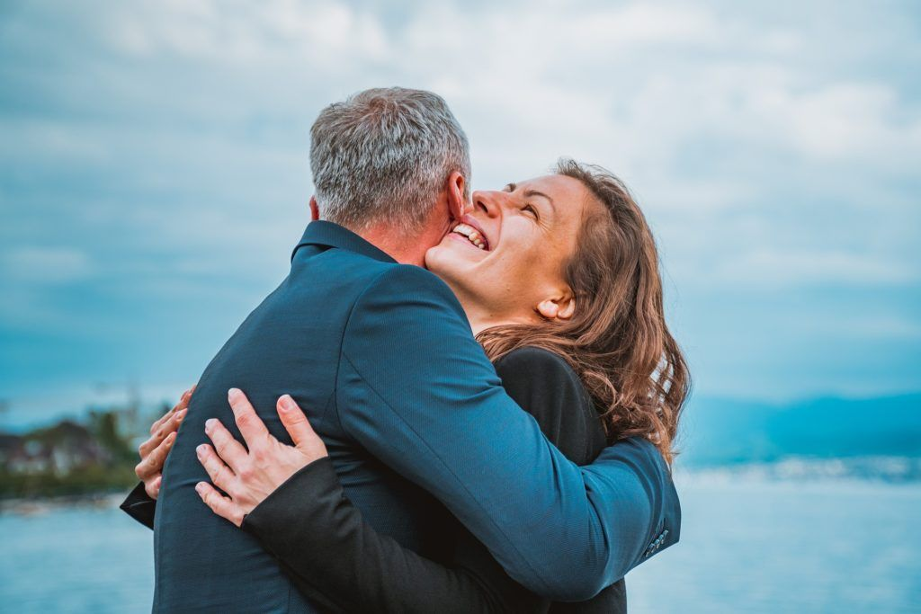 Dwoje przytulających się ludzi, kobieta i mężczyzna, widoczna uśmiechnięta twarz kobiety i siwiejąca głowa mężczyzny. Rozmyte niebieskie tło, chyba nad morzem.